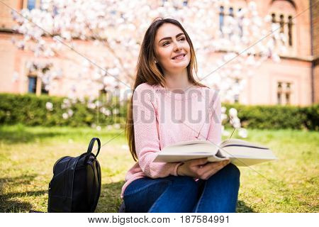 Young, Charming Girl Student Reads Book Against Background Of Green Grass And Blossom Tree