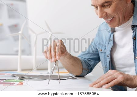 Charged with positivity. Joyful smiling engineer sitting at the table and drawing a blueprint with compasses