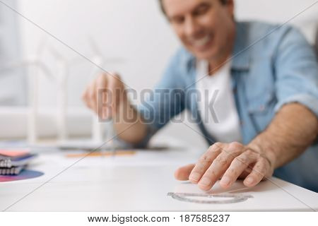 Lets start working. Close up of drawing tools in hands of positive pleasant skillful engineer working on the blueprint