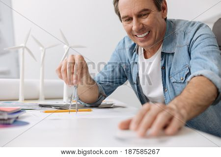 Full of gladness. Cheerful content skillful engineer sitting at the table and drawing a blueprint while working in the office