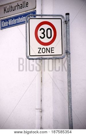 On a house corner are a road sign and a signpost placed next to an speed limit sign.
