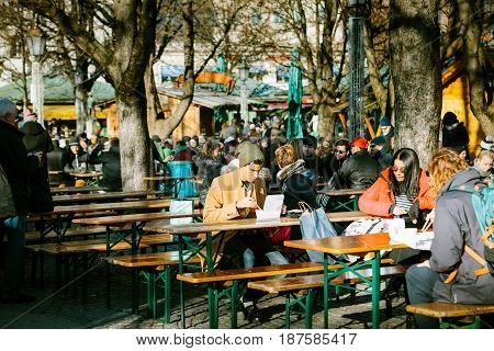 Munich, Germany, December 29, 2016: A young man eats in street coffee with fast food and national food near the central square of Munich - Marienplatz.