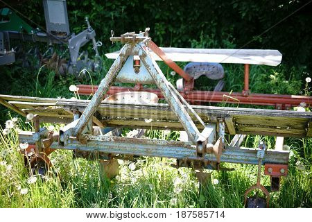An old rusted plow stands on a wild meadow and is overgrown.
