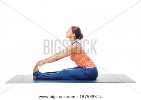 Woman doing Ashtanga Vinyasa Yoga asana Paschimottanasana - seated forward bend pose isolated on white background