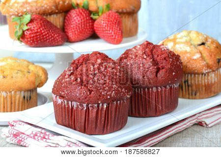 Variety of delicious breakfast muffins served on platters with strawberries