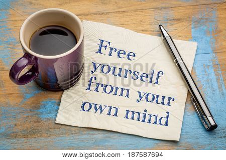 Free yourself from your own mind - inspirational handwriting on a napkin with a cup of espresso coffee