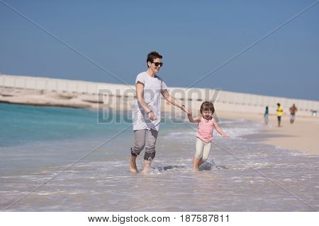 beautiful young mother and cute little girl are enjoying while running on exotic beach along the ocean Travel and Vacations.