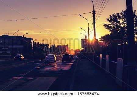 Warm urban scene at sunset, beautiful evening sunset, city traffic, cars on the bridge, city life concept, toned