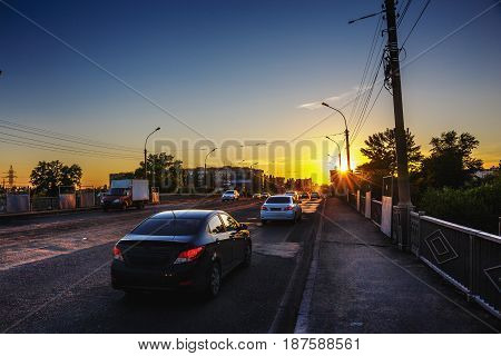City traffic, cars on the bridge at sunset time in evening light, city life concept, toned