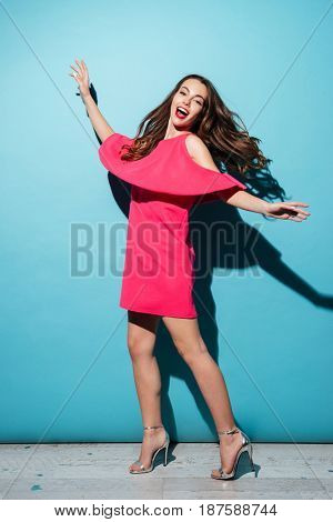 Full length portrait of a smiling pretty girl in dress posing isolated over blue background