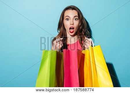 Portrait of a shocked pretty girl holding colorful shopping bags isolated over blue background