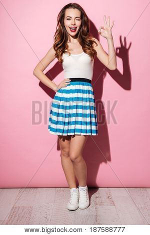 Portrait of a pretty young girl showing ok gesture and winking over pink background