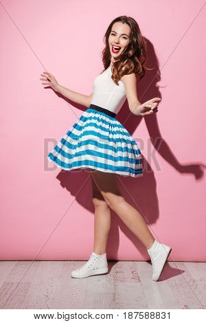 Full length portrait of a cheerful young girl wearing dress and dancing over pink background