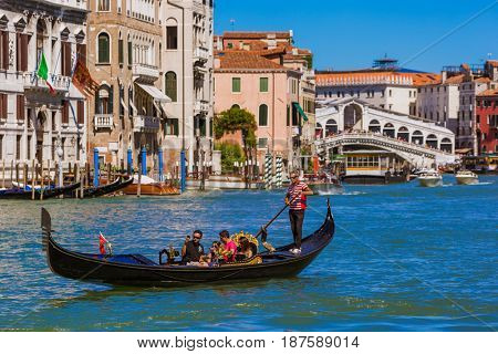 VENICE, ITALY - AUGUST 22, 2016: Tourists ride in gondola near Rialto bridge on August 22, 2016 in Venice Italy.