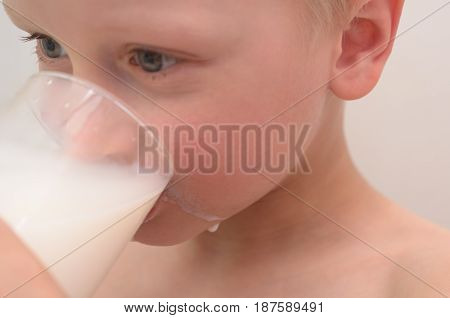 The boy drinks milk from a glass for breakfast