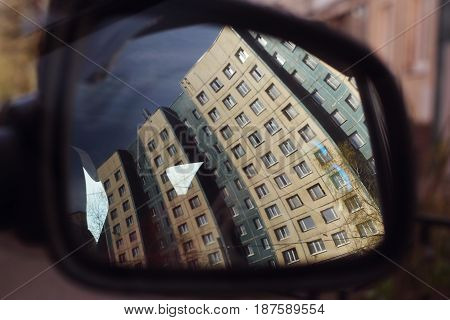Car side window with houses reflection in it