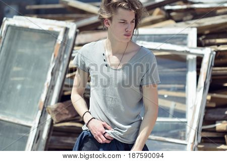 Portrait of young handsome man over wood boards, outdoor. Attractive trendy fashion 18 years old teen boy posing outside over debris, image toned