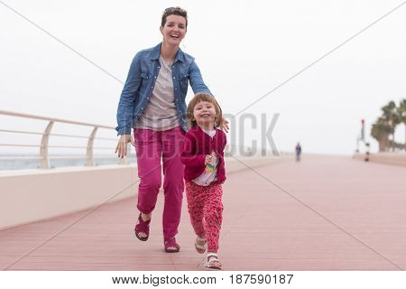 young mother and cute little girl running and cheerfully spend their time on the promenade by the sea