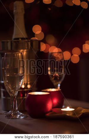 champagne and crystal glasses on a wooden table with candles and holiday lights in the background