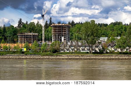 Construction of a new high-rise buildings in the city side of the riverbank in city of Vancouver