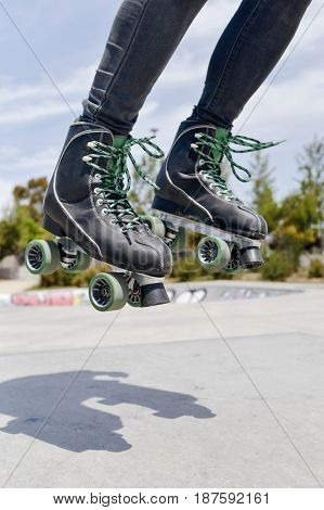 closeup of a young caucasian man roller skating with quad skates jumping in an outdoors skate park