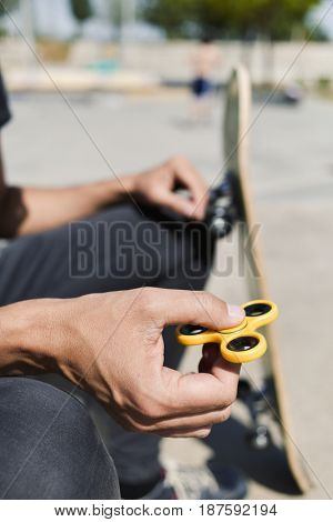 closeup of a young caucasian man in a skatepark playing with a yellow fidget spinner