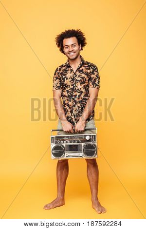 Picture of young happy african man standing with tape recorder isolated over yellow background. Looking at camera.