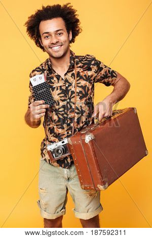 Photo of young happy african man standing isolated over yellow background. Looking at camera holding passport and suitcase.