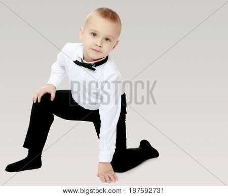 Elegant little boy in black pants , white shirt and black tie. Standing on one knee.On a gray background.