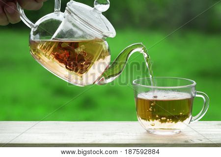 Filling cups tea making tea drinking karkade on the veranda nature