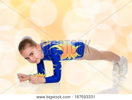 Beautiful Russian girl gymnast younger school age, in blue in a sports swimsuit.The girl does the rack on elbows.Brown festive, Christmas background with white snowflakes, circles.