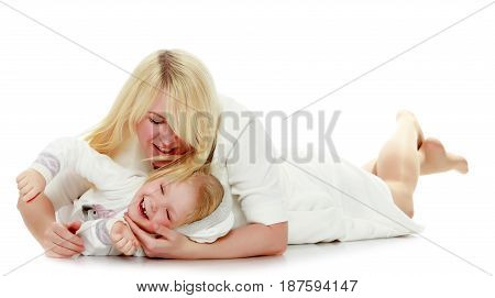 Happy family mother and little daughter lying on the floor and gently hug.Isolated on white background.