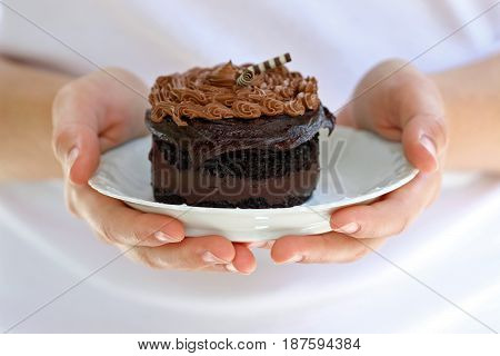 Two hands presenting a decadent chocolate cake on a white plate.