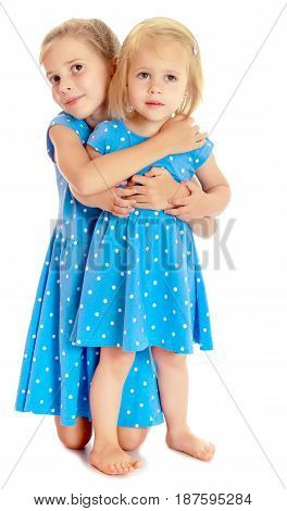 Two charming little girls, sisters , in identical blue dresses with polka dots , cuddling.Isolated on white.