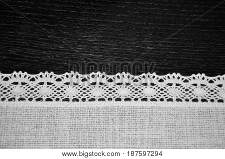 Beautiful black and white lacy lace white embroidery linen textile on wooden desk background