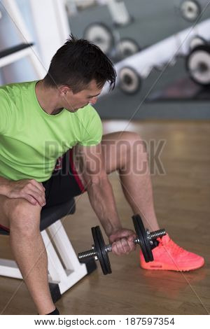 young handsome man working out with dumbbells in a fitness gym
