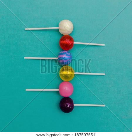 Six colorful round lollipops are lying in a row on a light blue background One-color and two-color candies
