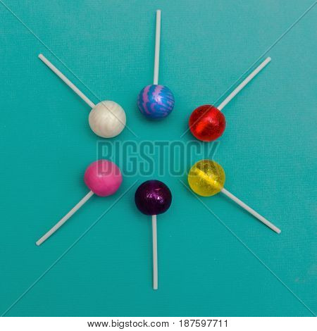 Six colorful round lollipops are lying on a light blue background One-color and two-color candies
