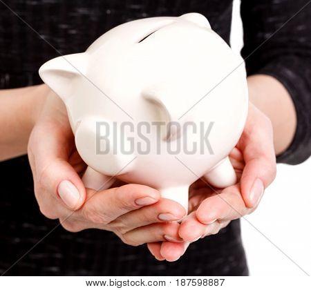Closeup shot of woman's hands holding a piggy bank