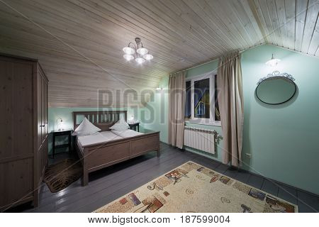 Interior of room with double bed, wardrobe, carpet in hotel.