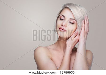 beautiful young blond woman with short blond hair against grey studio background