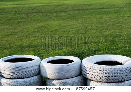 Painted white old tires on kart race course over green grass background