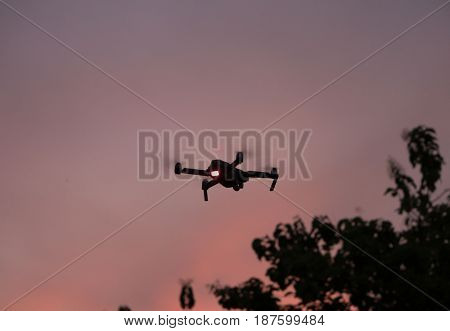 Silhouette of flying drone against beautiful sunset sky background