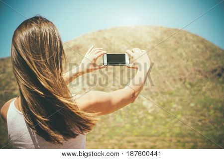 Young woman taking some photo with her mobile smartphone of her travel in summer - Tourist hiking the mountain taking pictures for her social media - Lifestyle people and travel concept