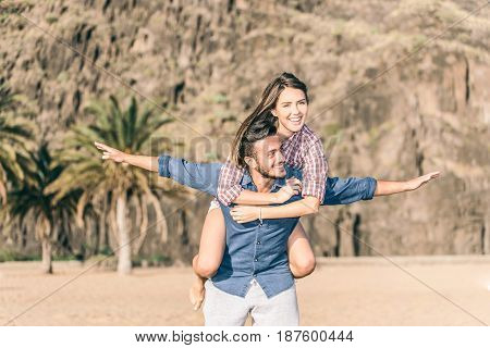 Handsome man carrying girlfriend on his back in a beautiful beach on a sunny day - Fashion couple of lovers in vacation having fun on the beach with a mountain in the background - Vintage filter