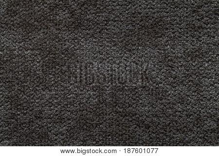 Black fluffy background of soft fleecy cloth. Texture of light dark gray nappy textile closeup.