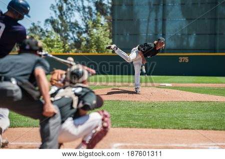 Baseball pitcher following through to pitch to right handed batter.