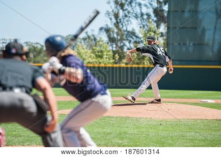Baseball pitcher winding up to pitch to left handed batter.