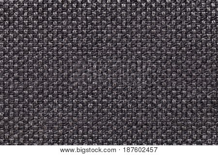 Dark brown background with checkered pattern closeup. Structure of the black fabric macro.