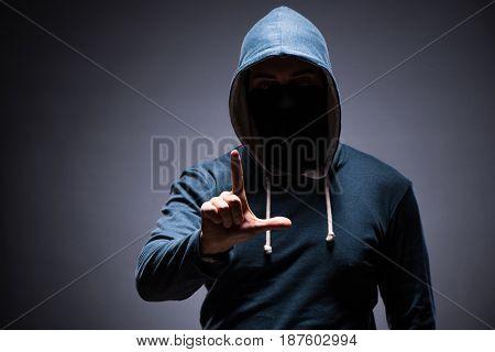 Man wearing hood in dark room